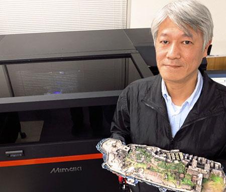 Susumu Fukunaga, Executive Director, standing in front of the
